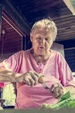 Senior woman pealing potatoes. Granny cooking delicous food Stock Images