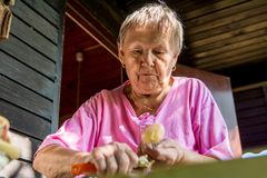 Senior woman pealing potatoes. Granny cooking delicous food Royalty Free Stock Image