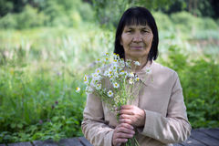 Senior woman pensioner outside with camomile Royalty Free Stock Image