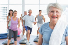 Senior woman with people exercising in fitness studio Stock Photos