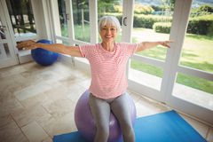 Senior woman performing stretching exercise on fitness ball. At home Royalty Free Stock Photos
