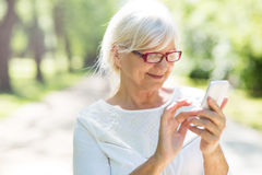 Senior woman on the phone. Happy senior woman smiling outdoors Stock Photography