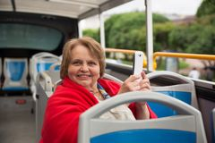 Senior woman with phone on a tour bus, Saint Royalty Free Stock Images