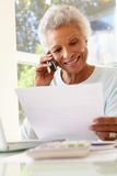 Senior Woman On Phone Using Laptop At Home Royalty Free Stock Images
