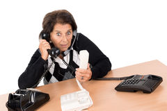 Senior woman with phones. Desperate senior woman with several phones isolated in white Stock Image