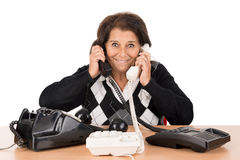 Senior woman with phones. Desperate senior woman with several phones isolated in white Stock Images