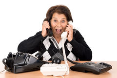 Senior woman with phones. Desperate senior woman with several phones  in white Stock Photography