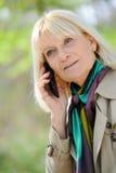 Senior woman phoning. Senior woman happy phoning outdoor Royalty Free Stock Image