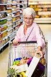 Senior woman picking corn flakes Royalty Free Stock Photography