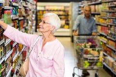 Senior woman picking out product. Senior women picking out product in supermarket Stock Photo