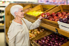 Senior woman picking out red apple Stock Photography