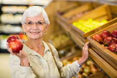 Senior woman picking out a red apple Stock Photography