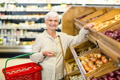 Senior woman picking out some vegetables. In supermarket Stock Image