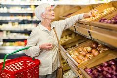 Senior woman picking out some vegetables. In supermarket Royalty Free Stock Photos