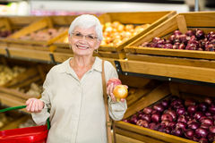 Senior woman picking out some vegetables. In supermarket Stock Photography
