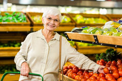 Senior woman picking out some vegetables. In supermarket Stock Images