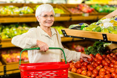 Senior woman picking out some vegetables. In supermarket Stock Photo