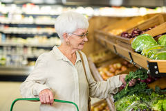 Senior woman picking out some vegetables. In supermarket Royalty Free Stock Photo