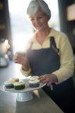 Senior woman picking up the cupcake from the tray Stock Images