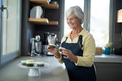 Senior woman picking up the cupcake from the tray Royalty Free Stock Image