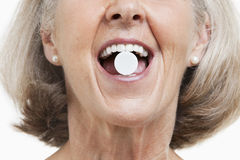 Senior woman with a pill between her teeth against white background Stock Image
