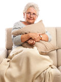 Senior woman with pillow and blanket Stock Images