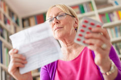 Senior woman with pills and prescription stock photography