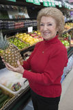 Senior Woman With Pineapple In Supermarket Stock Images