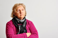 Senior woman in pink with crossed arms Stock Images