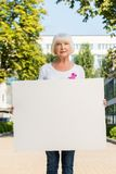 Senior woman with pink ribbon holding blank banner and looking at camera breast cancer awareness. Concept stock photo