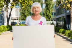 Senior woman with pink ribbon holding blank card and looking at camera breast cancer awareness. Concept royalty free stock photos