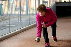 Senior woman playing Bowls in position. Senior or an older woman in a pink sport suit  playing Bowls ready to throw a bawling ball or to bowl on a track in the Royalty Free Stock Images