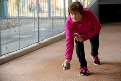 Senior woman playing Bowls. Senior or an older woman in a pink sport suit  playing Bowls ready to throw a bawling ball or to bowl on a track in the afternoon Stock Image