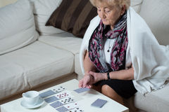 Senior woman playing cards alone Royalty Free Stock Photos