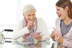 Senior woman playing cards. Happy senior women playing cards with eldercare nurse Royalty Free Stock Image