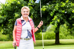 Senior woman playing golf on course holding flag Stock Photo