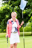 Senior woman playing golf on course holding flag Stock Photography