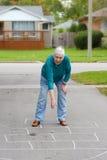 Senior woman playing hopscotch Stock Photo