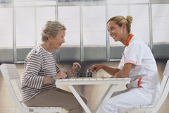 Senior woman playing with  nurse in retirement Stock Photo