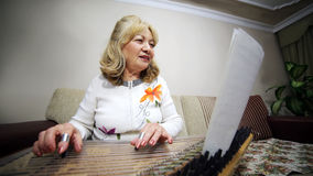 Senior woman playing qanun instrument Stock Photos