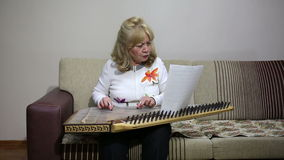 Senior woman playing qanun instrument Royalty Free Stock Photo