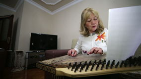 Senior woman playing qanun instrument Royalty Free Stock Images