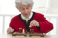 Senior woman playing at retirement home. Portrait of an elderly woman playing chess  fully concentrated Stock Image