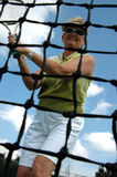 Senior woman playing tennis. An active senior woman on the tennis court as seen through the net (focus on woman stock photos