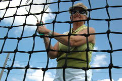 Senior woman playing tennis. An active senior woman on the tennis court as seen through the net (focus on woman stock photography