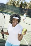 Senior Woman Playing Tennis In Court Stock Images