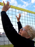 Senior woman playing volleyball on beach Royalty Free Stock Image