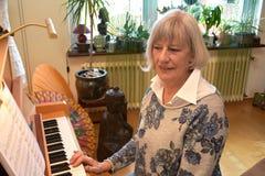 Senior woman plays piano Royalty Free Stock Photo