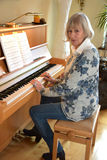 Senior woman plays piano Stock Photos