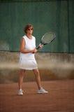 Senior woman plays tennis Royalty Free Stock Image